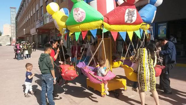 """Kinder spielen auf dem Karussell und vor der Kulisse des Hotan-Marktes machen """"Hauswächter"""" ihre Übungen."""