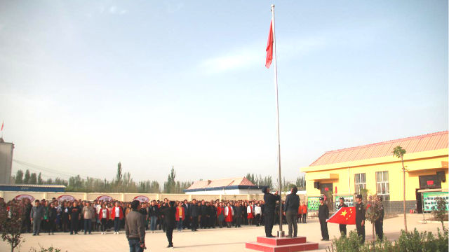 Die Menschen in einem Ort in Xinjiang sind organisiert, um eine Fahnenhebezeremonie abzuhalten